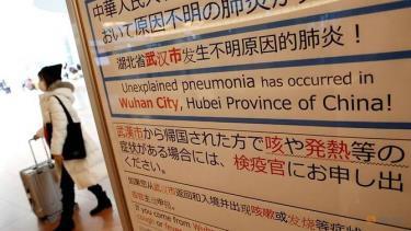 Một phụ nữ đeo khẩu trang đi qua một cảnh báo về dịch bệnh ở Vũ Hán ở sảnh đến sân bay Haneda, Tokyo.