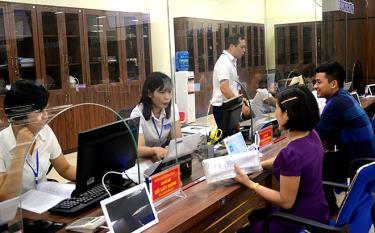 Cán bộ Trung tâm Phục vụ Hành chính công tỉnh Yên Bái giải quyết thủ tục hành chính cho người dân. (Ảnh: Đức Toàn)