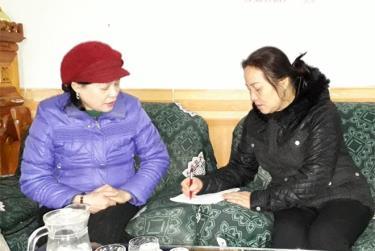 Bà Nguyễn Kim Dung (áo đen) đang tư vấn chính sách bảo hiểm y tế tự nguyện cho khách.