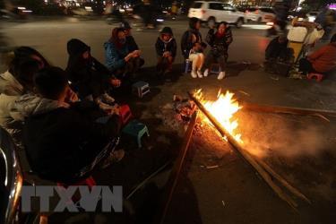 Nhiều người quây quần bên đống lửa để sưởi ấm.