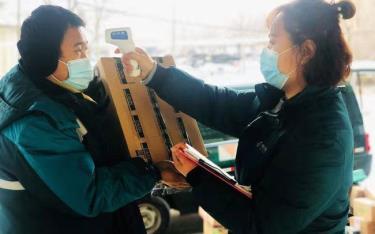 Nhân viên bưu điện Đại Hưng kiểm tra thân nhiệt trước khi giao hàng.