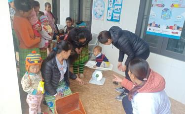 Mothers in the nutrition club of Phinh Ho commune, Tram Tau district work with the local health station to keep track of their children's growth.