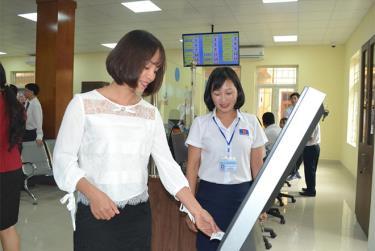 Cán bộ Bộ phận Phục vụ hành chính công thành phố Yên Bái hướng dẫn quy trình giải quyết công việc cho người dân.