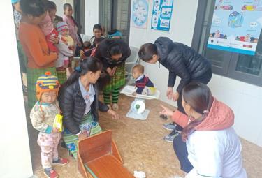 Các bà mẹ trong Câu lạc bộ dinh dưỡng xã Phình Hồ, huyện Trạm Tấu phối hợp với trạm y tế xã theo dõi sự phát triển của trẻ. (Ảnh: Minh Huyền)