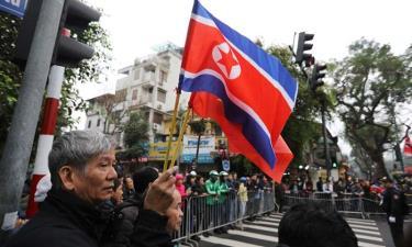 Người dân cầm cờ Việt Nam và Triều Tiên đứng chờ đoàn xe của Chủ tịch Kim Jong-un gần khách sạn Melia ở Hà Nội.