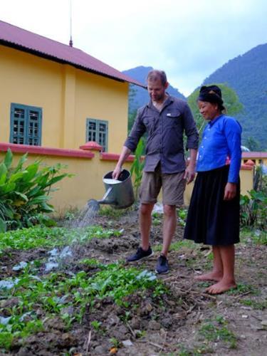 Khách du lịch nước ngoài trải nghiệm công việc làm vườn cùng người dân tại homestay Xôi, xã Lâm Thượng, huyện Lục Yên.