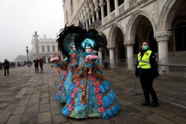 Một nữ cảnh sát đeo mặt nạ đứng cạnh những người vui chơi lễ hội tại Venice Carnival, ngày 23/2.