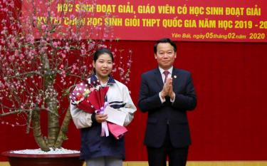 Chairman of the provincial People's Committee Do Duc Duy presents a reward to Bui Thi Nhung, a 12th grader of the Nguyen Tat Thanh High School for the Gifted, who earned a score of 17 out of 20 points to win the first prize at the national contest on geography for the 2019-2020 academic year.