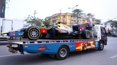 The F1 model car is carried on a truck during the parade in Hanoi on February 22.