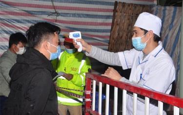 Cán bộ Trung tâm Y tế huyện Trấn Yên đo thân nhiệt cho người dân tại chốt kiểm dịch thôn Linh Đức, xã Minh Quân. (Ảnh: Quyết Thắng)