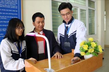 Thầy giáo Đặng Tiến Thành (đứng giữa) cùng các em Vũ Mai Hồng và Nguyễn Đức Chiến giới thiệu sáng chế bục phát biểu thông minh.