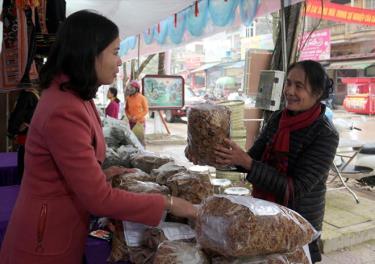 Chị Vũ Thị Hồng Duyên (bên trái) giới thiệu sản phẩm măng khô cho khách hàng.
