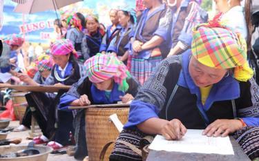Phụ nữ Mông Mù Cang Chải thi vẽ hoa văn bằng sáp ong trên vải.