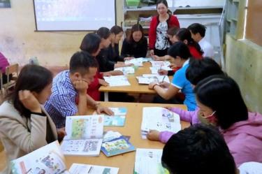 Teachers at Phuc Son primary school in Nghia Lo town, Yen Bai province, study sample textbooks.