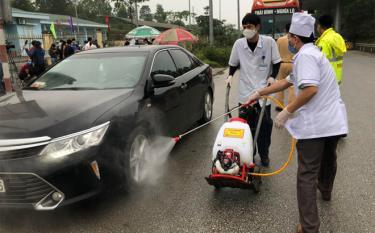 Phun khử trùng phương tiện tại chốt kiểm dịch y tế liên ngành (Ảnh: Hồng Duyên)