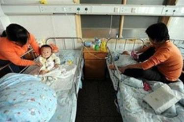 Hai phụ nữ Trung Quốc đang chăm sóc con bị bệnh do sữa melamine tại một bệnh viện ở Hợp Phì, tỉnh An Huy.