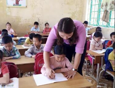 Cô giáo Đàm Thị Thanh Nga uốn nắn từng nét chữ cho học sinh.
