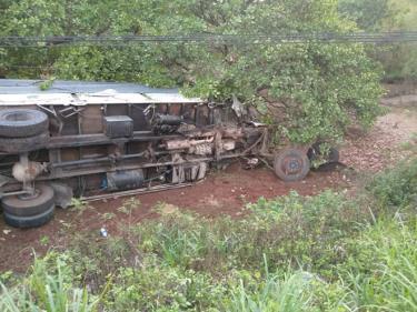 Sau tai nạn xe tải chở rau lao xuống vệ đường, lật ngang.
