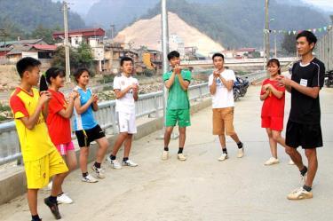 Cán bộ Trung tâm Truyền thông và Văn hóa huyện Mù Cang Chải hướng dẫn học sinh các bước khởi động trước khi tham gia hoạt động thể thao.