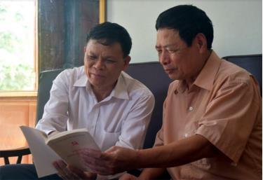 Ông Nguyễn Duy Thêm (bên phải) và ông Trần Quang Trung - Chủ tịch UBND xã Báo Đáp cùng nhau ôn lại truyền thống lịch sử Đảng bộ địa phương.