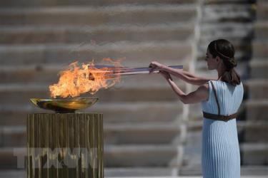 Diễn viên Hy Lạp Xanthi Georgiou trong trang phục nữ tư tế tối cao thắp ngọn đuốc Olympic trong lễ trao đuốc cho Nhật Bản tại Athens, Hy Lạp, ngày 19/3/2020.