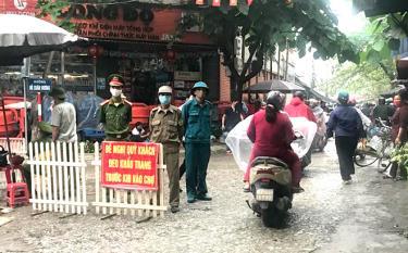 Các lực lượng chức năng giám sát việc người dân tuân thủ các quy định về phòng, chống dịch bệnh Covid-19 tại cổng chợ Yên Ninh (thành phố Yên Bái).