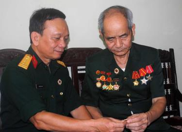 Cựu chiến binh Đỗ Quang Bình (bên phải) ôn lại những kỷ vật của đời lính.