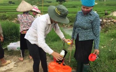 Cán bộ Trung tâm Dịch vụ hỗ trợ phát triển nông nghiệp huyện Trạm Tấu hướng dẫn nông dân cách pha thuốc bảo vệ thực vật.