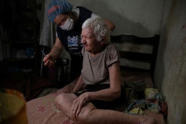 Bà Elisa Melo Marinho, 86 tuổi, được tiêm vắc-xin Covid-19 của AstraZeneca tại nhà ở khu ổ chuột Rocinha thuộc TP Rio de Janeiro - Brazil.