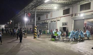 Nhân viên y tế thực hiện lấy mẫu xét nghiệm cho các công nhân tại Nhà máy sản xuất vải Din Han, thành phố Stung Meanchey, Campuchia.