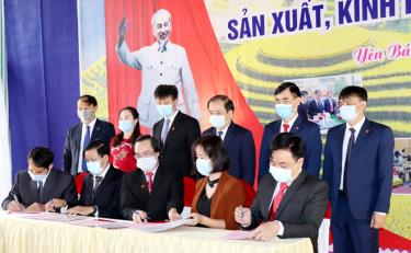 Leaders of Yen Bai witness the signing of a programme on using services and products of members of the Bloc of provincial units and enterprises in 2021.
