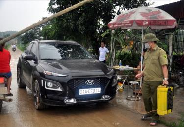 Lực lượng chức năng phun khử trùng các phương tiện giao thông ra, vào thôn Liên Hiệp, huyện Trấn Yên.