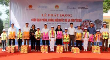 Đại diện lãnh đạo Sở Lao động, Thương binh và Xã hội, lãnh đạo UBND huyện Văn Yên tặng áo phao cho 6 trường tiểu học.