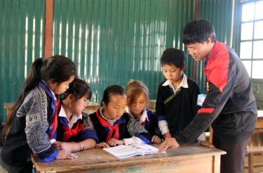 Giáo viên Trường Phổ thông DTBT Tiểu học và THCS Dế Xu Phình, huyện Mù Cang Chải hướng dẫn học sinh đọc sách, báo tại tủ sách nhà trường.