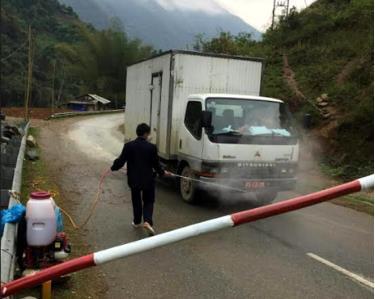 Phun tiêu độc khử trùng các phương tiện giao thông qua chốt kiểm dịch. (Ảnh: Hồng Duyên)