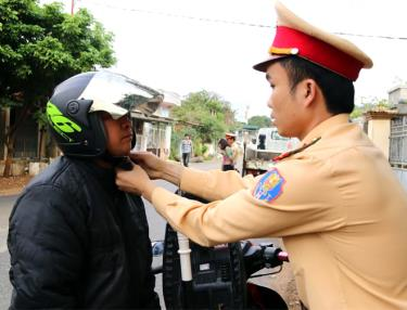 Cảnh sát giao thông huyện Văn Chấn hướng dẫn người dân đội mũ bảo hiểm đúng cách.