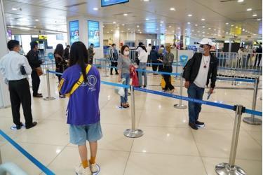 Hành khách tuân thủ khoảng cách tối thiểu khi làm thủ tục tại sân bay Nội Bài sau khi nới lỏng giãn cách xã hội.