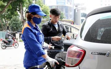 Nhân viên Petrolimex bán xăng cho khách hàng.