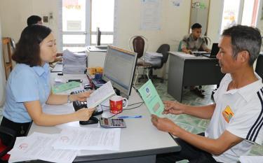 Cán bộ Bảo hiểm xã hội tỉnh Yên Bái bàn giao sổ bảo hiểm xã hội cho người lao động.