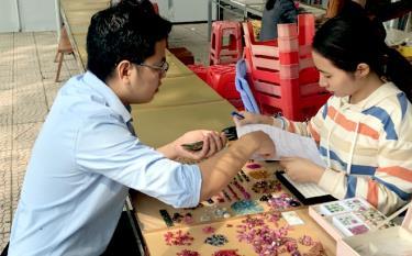 Cán bộ Bảo hiểm xã hội huyện Lục Yên tuyên truyền, vận động người dân tham gia bảo hiểm xã hội tự nguyện tại chợ đá quý.