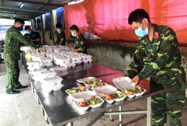 Officers and soldiers prepare meals for people staying in quarantine.