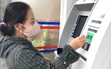 Nhận lương hưu qua thẻ ATM hạn chế việc tập trung đông người, phòng chống dịch bệnh Covid-19.