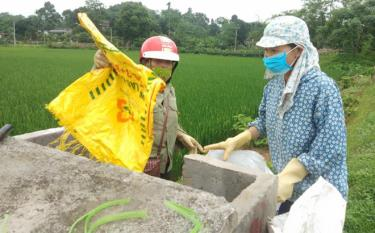 Residents put used pesticide bags into a tank on paddy fields