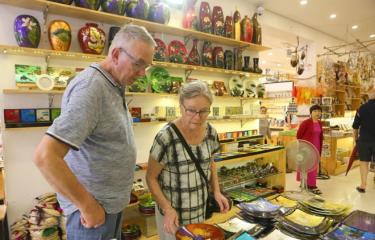 Khách du lịch quốc tế mua các sản phẩm lưu niệm tại Hàng Bông, Hà Nội.