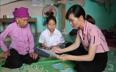 Cán bộ Lao động - Thương binh và Xã hội thị trấn Sơn Thịnh, huyện Văn Chấn tuyên truyền phòng chống xâm hại trẻ em tại gia đình bà Sa Thị Nít.