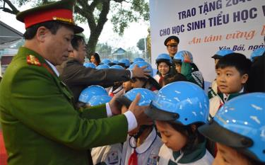 Lãnh đạo Ban An toàn giao thông tỉnh hướng dẫn học sinh Trường Tiểu học Mậu A, huyện Văn Yên đội mũ bảo hiểm đúng cách.