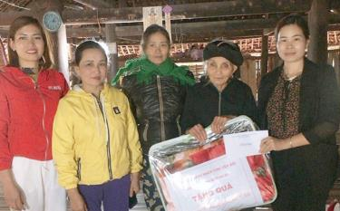Trieu Thi Minh Hien (right) presents pre-Tet gift packages to impoverished households on the behalf of the provincial businesswomen's association this year.