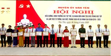 Chairman of the People's Committee of Van Yen district Ha Duc Anh presents certificates of merits to collectives and individuals with outstanding performance in studying and following President Ho Chi Minh's lifestyle and moral example in the 2016-2020 period.