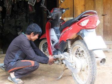 Nông dân huyện Mù Cang Chải sau khi học nghề sửa chữa xe máy đã mở hiệu sửa chữa tại nhà. (Ảnh: Thu Hạnh)