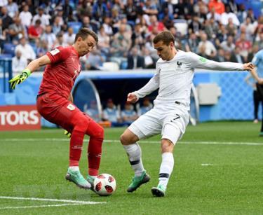 Thủ môn Fernando Muslera (trái) của Uruguay cản phá một pha bóng của Antoine Griezmann của Pháp trong trận đấu.